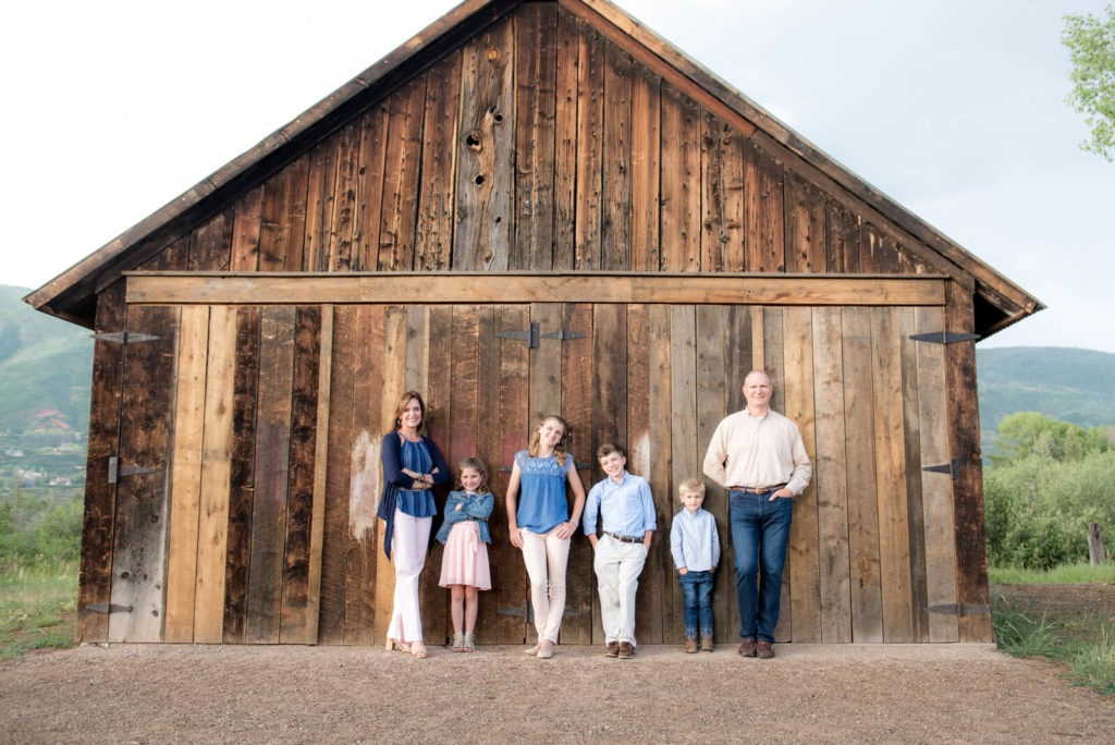 family portrait taken in front of an old barn