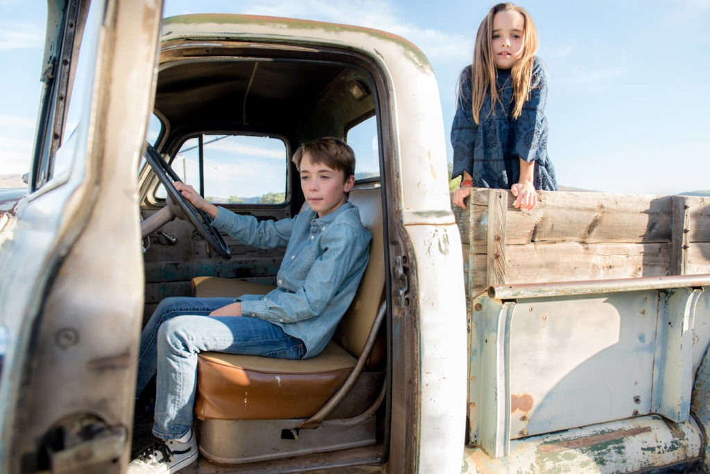 brother and sister posing in an old broken down truck
