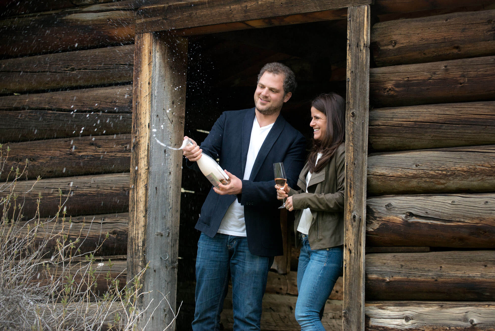 photo of a couple in the door of a rustic cabin popping champagne taken by Aspen photographer Michele Cardamone