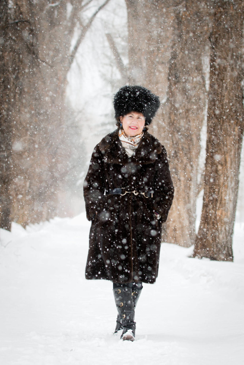 women walking while its snowing dressed in a fur coat and hat