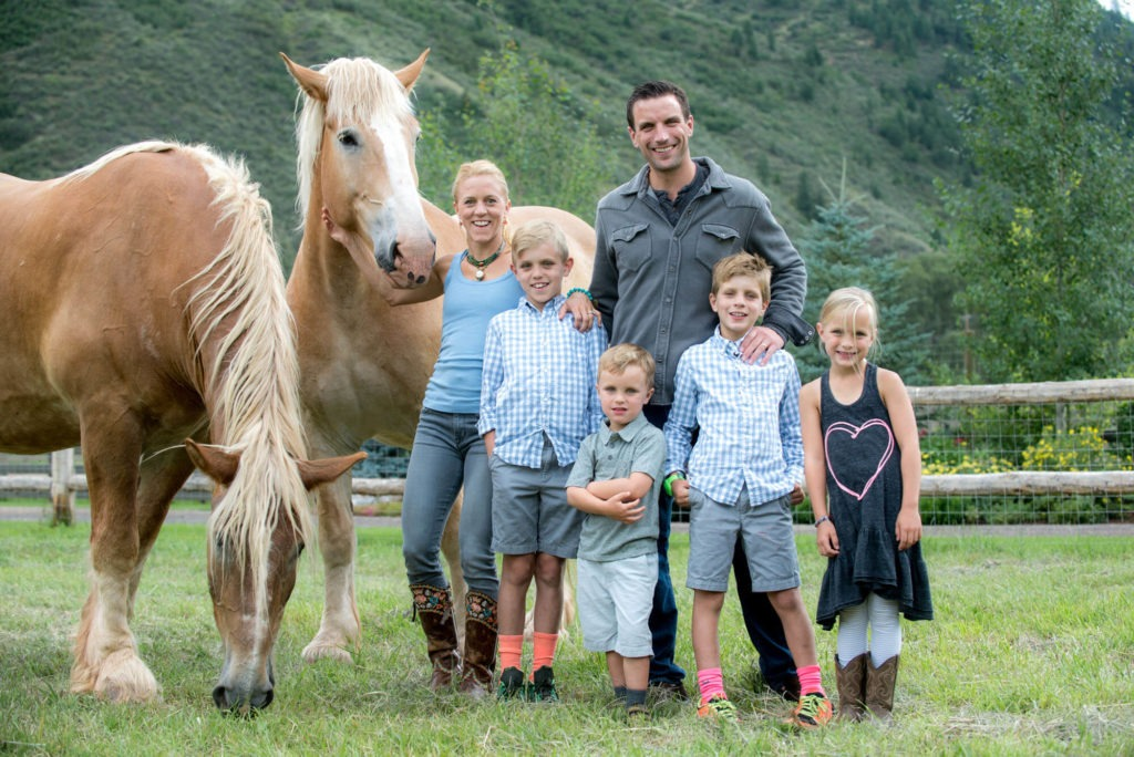family portrait in a field with horses taken by Michele Cardamone