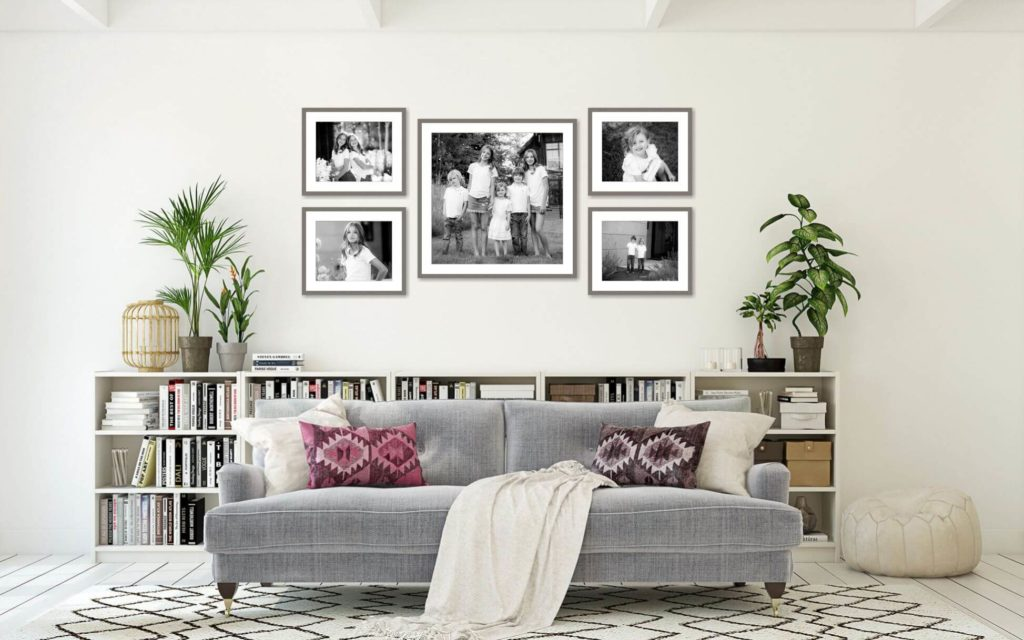 Framed family portrait gallery above living room couch