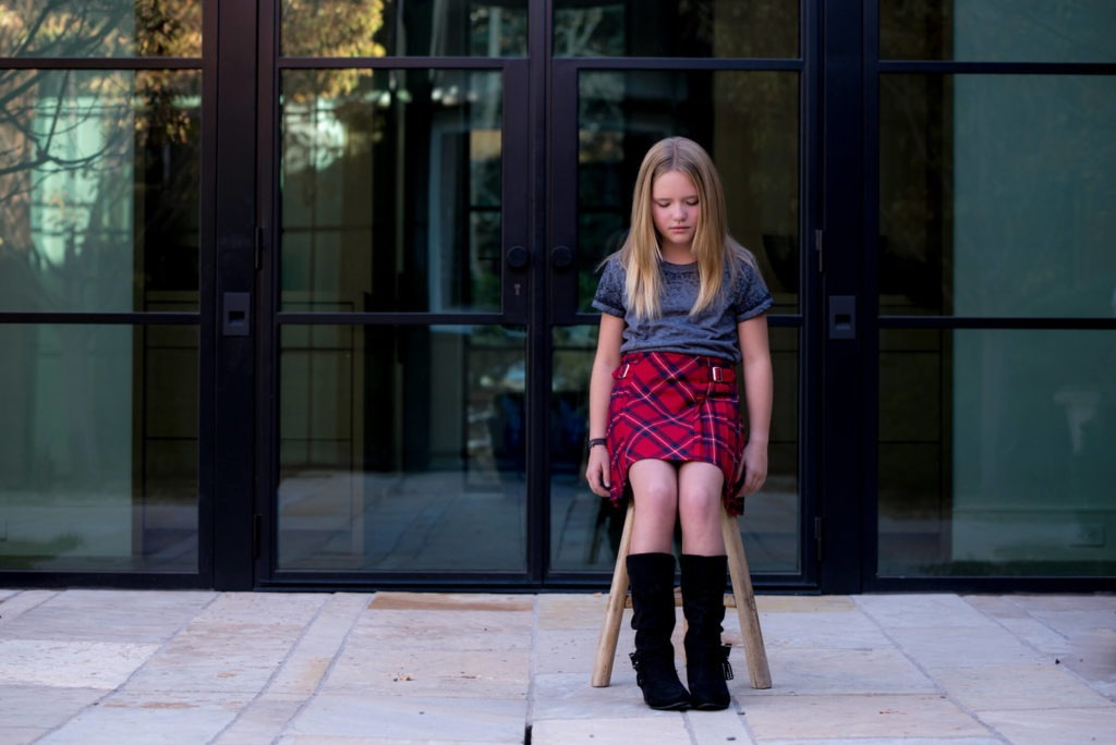 little girl in a red plaid skirt at her home