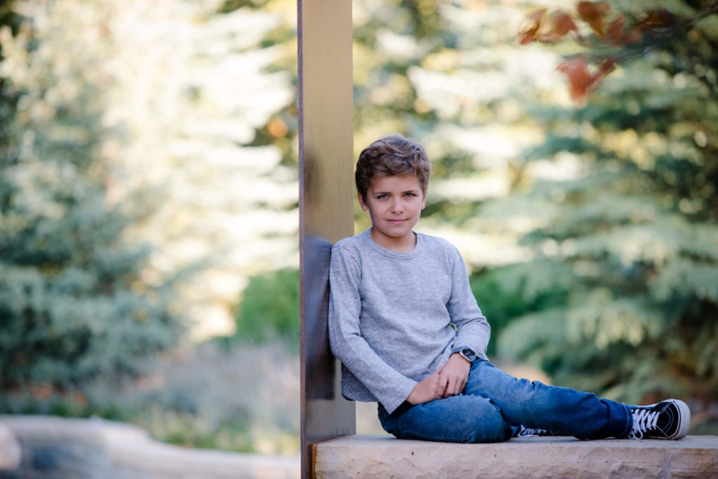 little boy on stone wall on a fall day