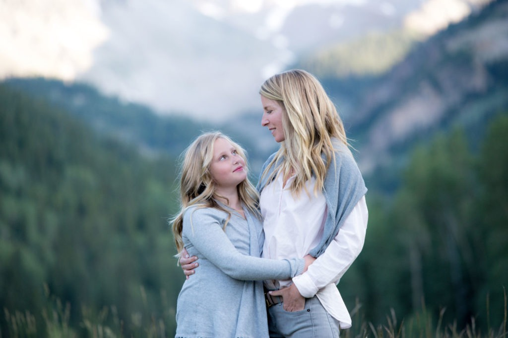Mother and daughter embrace with mountain backdrop