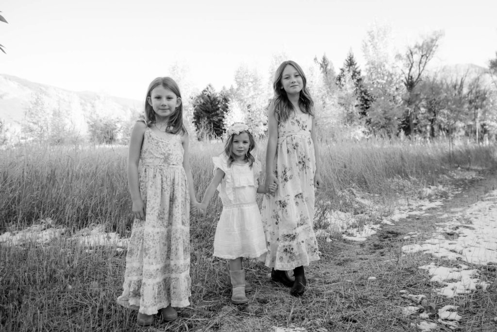 sisters holding hands in summer dresses on a fall day