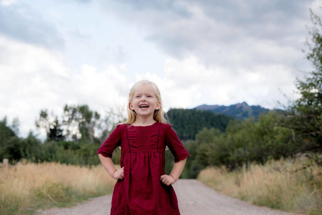 child portrait taken outside of a little girl in the fall