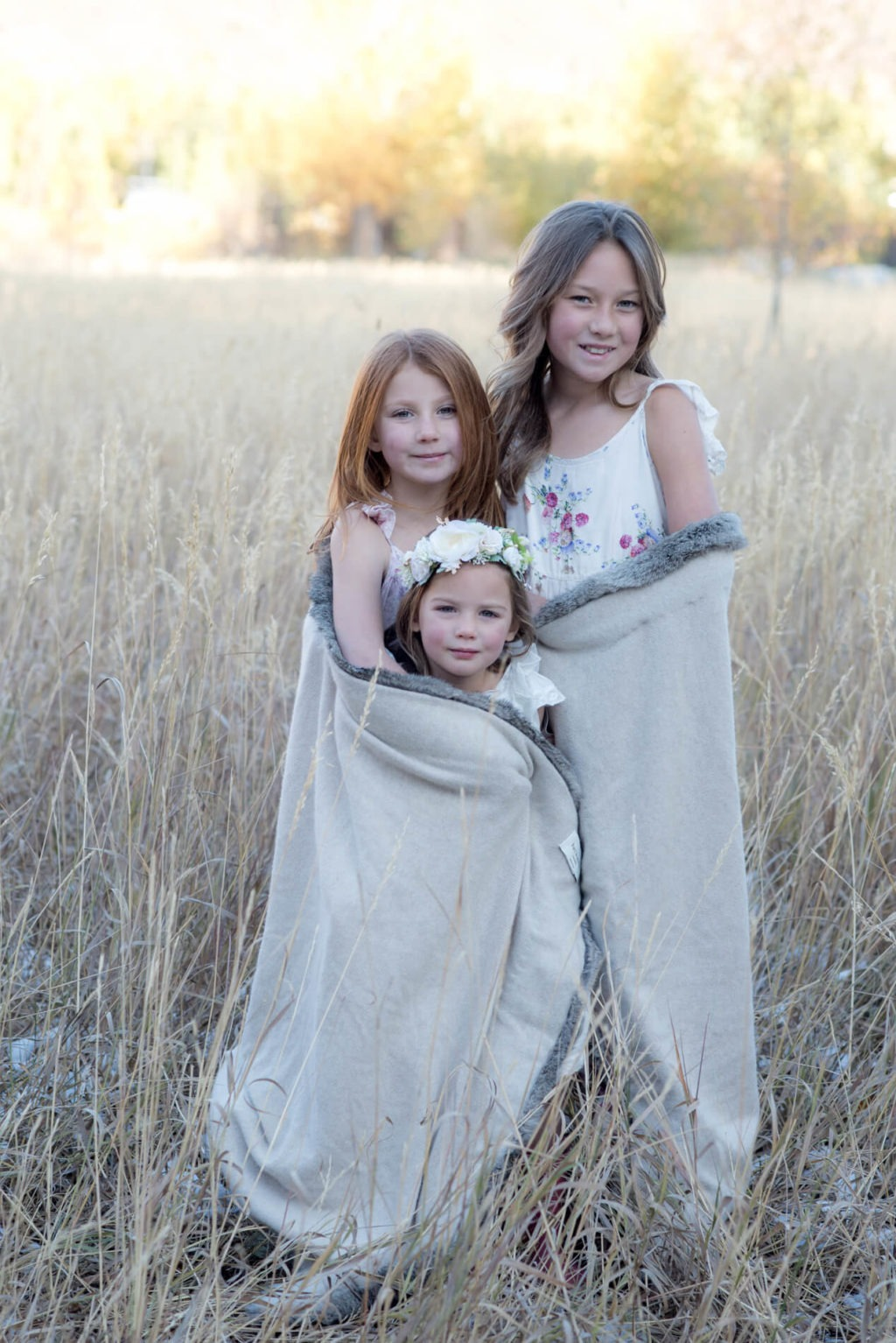 3 sisters wrapped tightly in a blanket