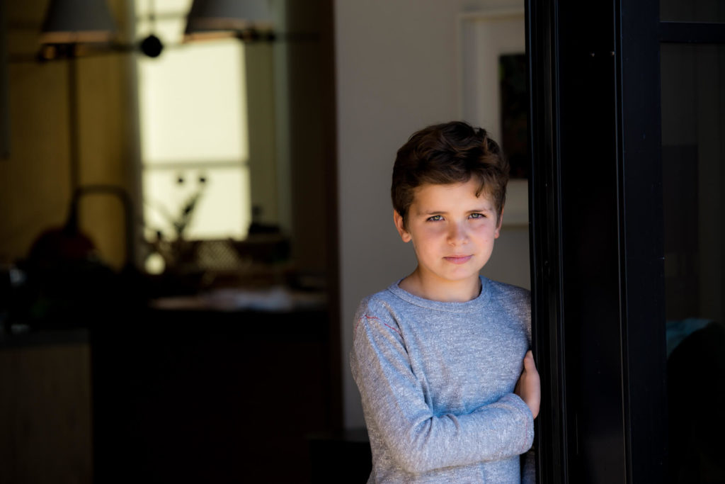 soulful portrait of a young boy at home