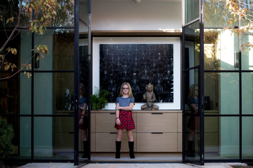 Young girl in entry of her home in plaid skirt