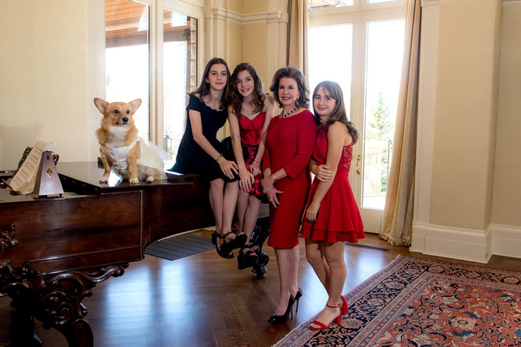 Indoor holiday portrait with mother and daughters and dog on the piano