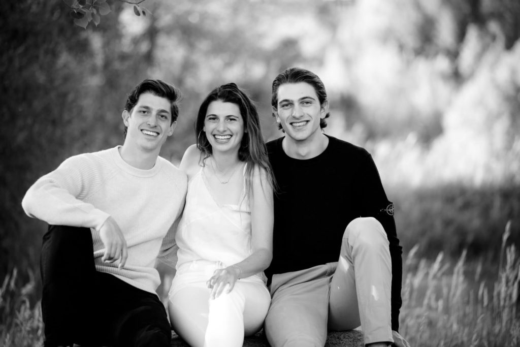 outdoor portrait of a girl and her two brothers sitting on a rock